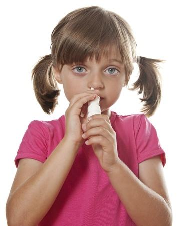 nasal: little girl using nasal spray - white background Stock Photo