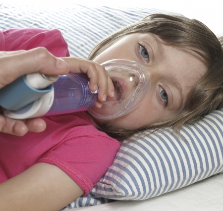 bronchitis: little girl with inhaler - respiratory problems for asthma