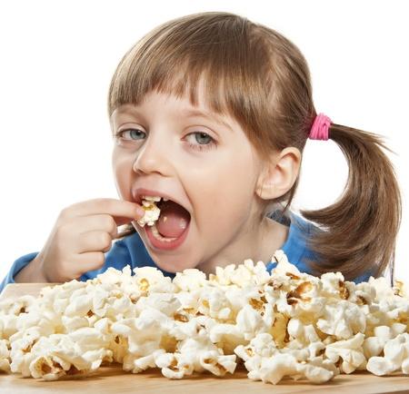 niños comiendo: niña feliz litle comiendo palomitas de maíz