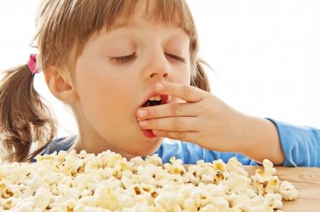litle:  litle girl eating popcorn