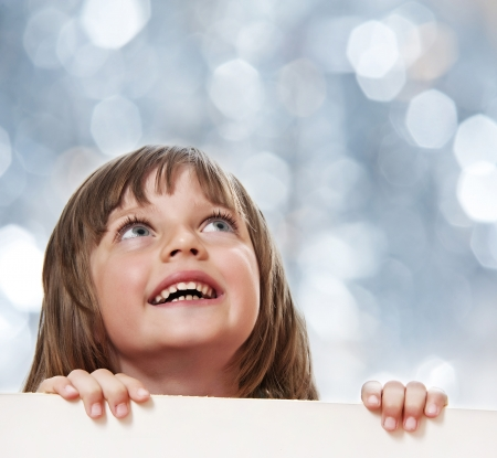 little girl with  white board with empty space - bokeh background photo