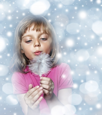 little girl blowing into white feather on christmas winter background photo