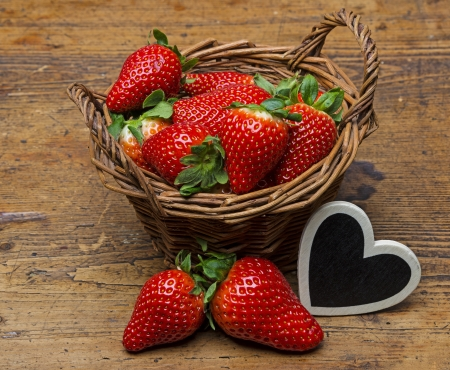 fresh strawberries in a basket - wooden  background photo