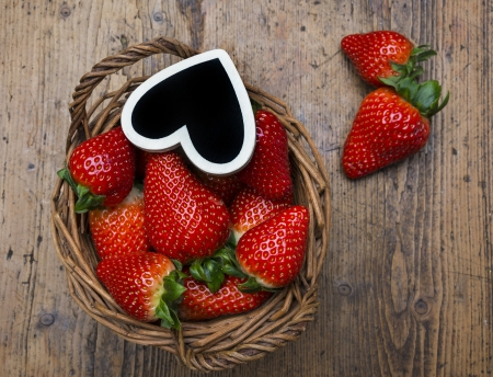 strawberries in a basket on a wooden  background photo