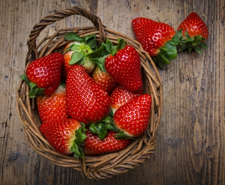 strawberry baskets: strawberries in a basket - wooden  background