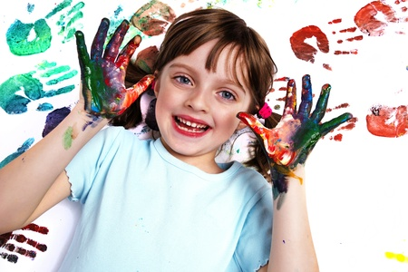 portrait of a happy school girl playing with water colors photo