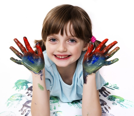 happy little girl playing with colors - white background photo
