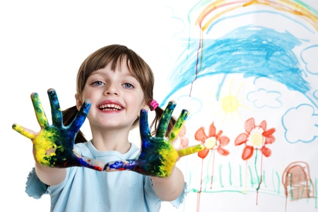 little girl with dirty hands painting her happy picture photo
