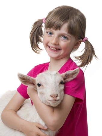 happy little girl with little goat isolated on white background photo