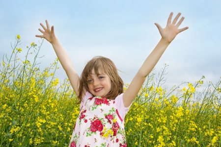 hayfever: happy little girl on a field with flowering colza Stock Photo