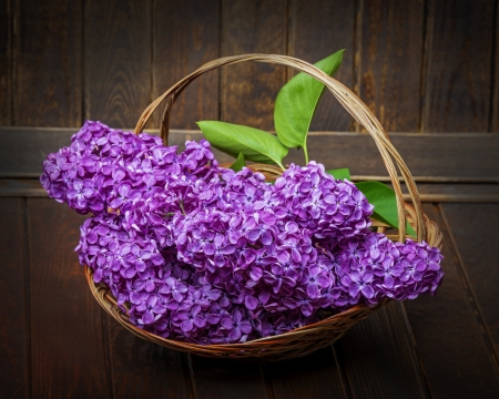 pink lilac in a basket and old wooden background photo