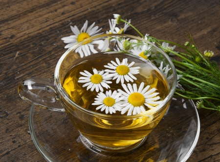 glass cup of camomile tea on a wooden table photo