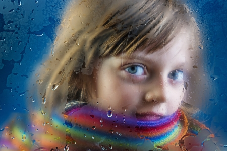 cold weather: rainy autumn - face of a little girl behind a dewy window Stock Photo