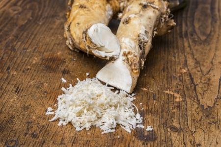 a grated horseradish on a kitchen table Standard-Bild