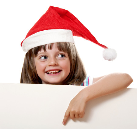 little girl with santa cap pointing on  white board with empty space for text photo