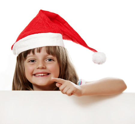 happy little girl with santa cap holding  white board with empty space photo