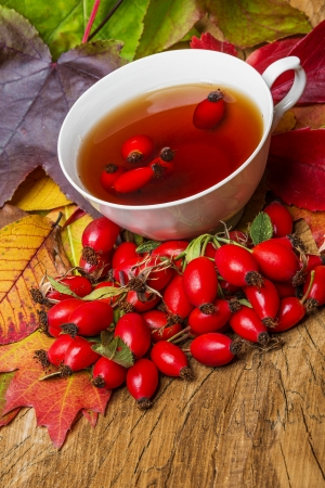 rosehip tea and autumn leaves photo