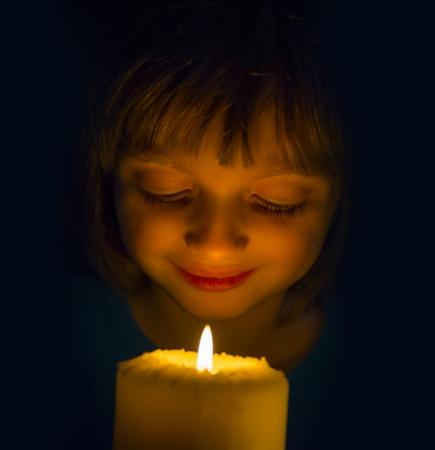 personas orando: niña feliz con una vela Foto de archivo