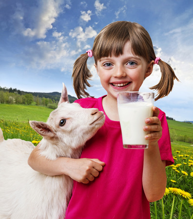little girl with a goat on a spring meadow  photo