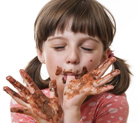 liten flicka äter choklad