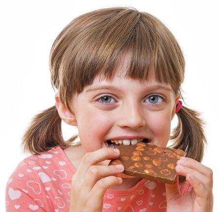 어린 소녀: 초콜릿 먹는 어린 소녀 스톡 사진
