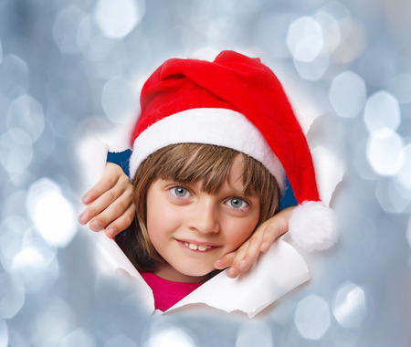 little girl with santa cap looking out of a hole in a paper photo