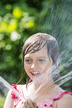 little girl smiling: little girl playing with water