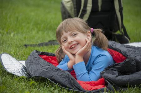sleeping bag: little girl camping with sleeping bag Stock Photo
