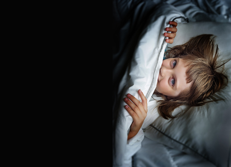 awake: little girl sleaping in a bed Stock Photo