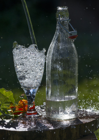 Glass with mineral water on the garden table