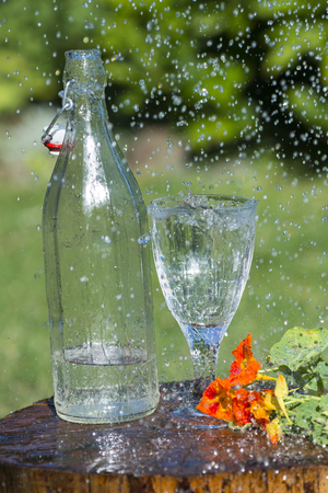 Glass with mineral water in the garden in rain Stock Photo