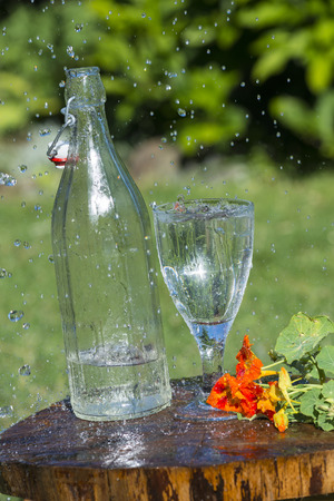 Glass with mineral water in rain Stock Photo