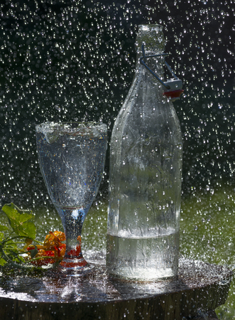 Glass with mineral water on the garden table in rain