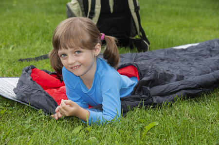 little girl camping with sleeping bag Stock Photo