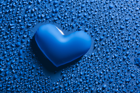 a heart shape between blue water drops - love concept