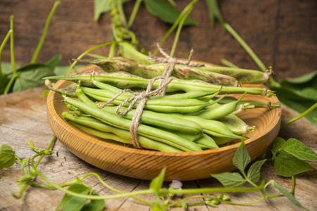 Fresh green beans on a wooden background