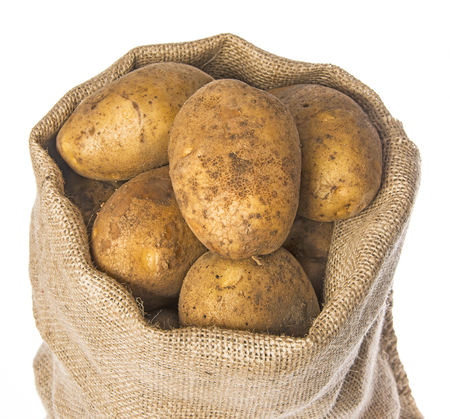 a fresh raw potatoes in a sack on a white background