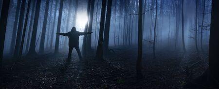 un uomo solo in una foresta oscura e nebbiosa Archivio Fotografico