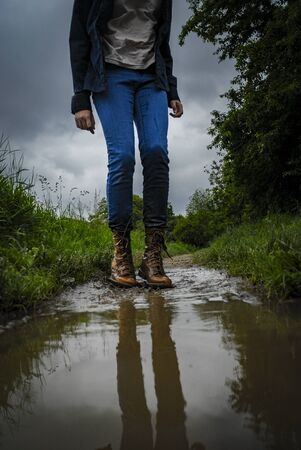 gitl with big boots is walking in a puddle 版權商用圖片