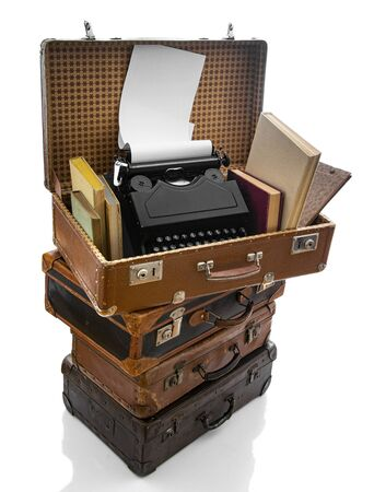 Old brown suitcases with old retro typing machine on a white background Stock Photo