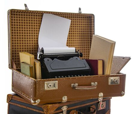 Old brown suitcases with old retro typing machine on a white background