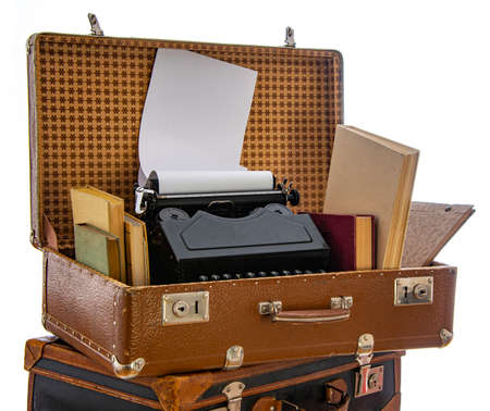 Old brown suitcases with old retro typing machine on a white background Stockfoto