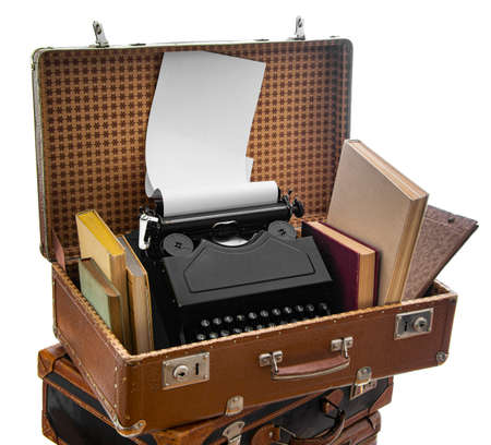 Old brown suitcases with old retro typing machine on a white background 版權商用圖片