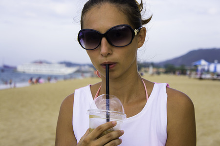 plastic cup: girl in sunglasses drinking coffee with a straw from a plastic cup on the beach. close-up Stock Photo