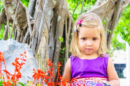 barrettes: little girl in a tropical garden. bonsai tree. Stock Photo