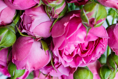shop tender: bouquet of beautiful pink peonies, roses with green leaves lie on a wooden table.