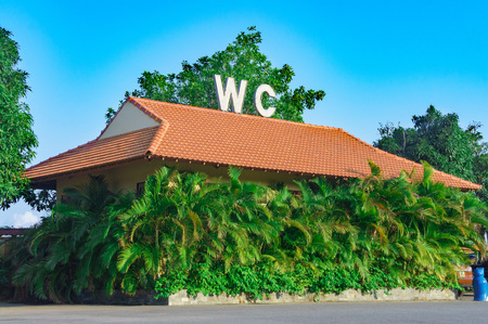 recreation room: toilet building surrounded by palm trees. on the roof of the large letters WC.