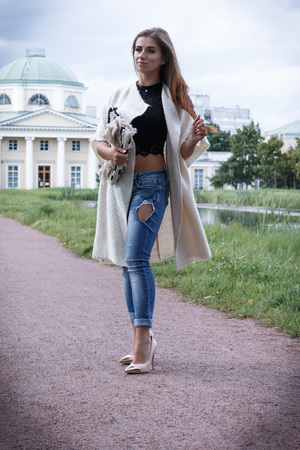 Outdoor fashion closeup portrait of nice pretty young hipster woman posing near a tower in jeans and shoes and a long cardigan