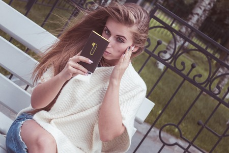 taking charge: irl sitting on a bench and looking at the phone as in a mirror, she adjusts makeup Stock Photo