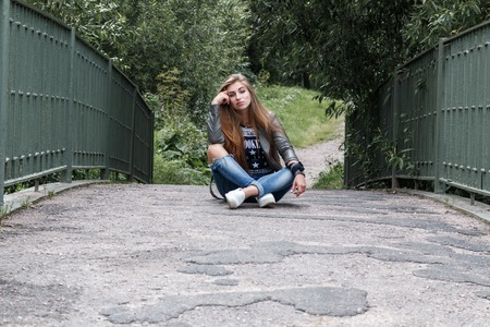legs folded: young beautiful teenager girl is sitting on the track on a bridge, rock n roll. rock style